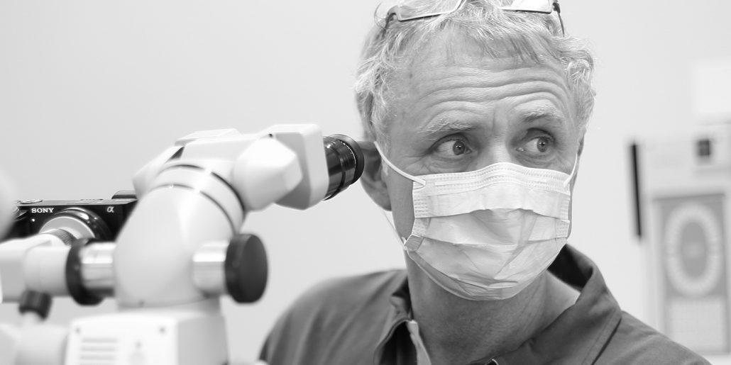 Zahnarzt Dr. Gauchel Düsseldorf - Spezialist für Endodontie - Wurzelbehandlung - mit Mikroskop schaut zur Assistenzkraft