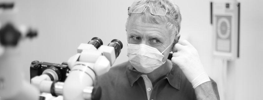 Zahnarzt Dr. Gauchel Düsseldorf - Spezialist für Endodontie mit Mikroskop - beim Abnehmen des Mundschutz