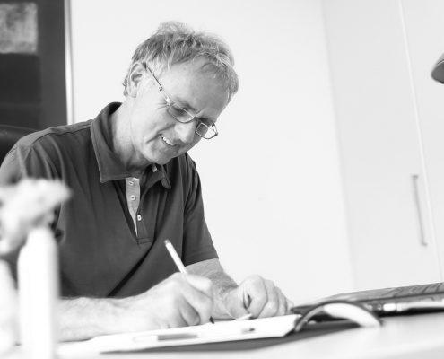 Endodontie - Zahnarzt Dr. Gauchel Düsseldorf Carlstadt bei der Prüfung eines Heil- und Kostenplans für eine Wurzelkanalbehandlung