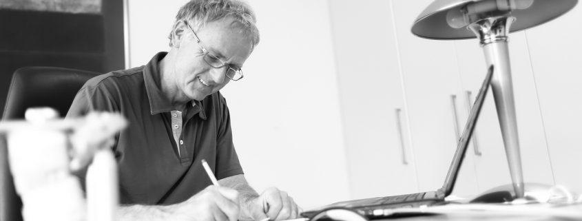 Zahnarzt Dr. Gauchel Düsseldorf Carlstadt bei der Prüfung eines Heil- und Kostenplans für eine Wurzelkanalbehandlung