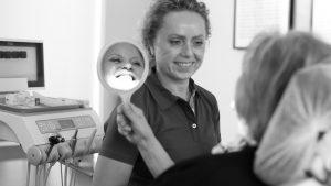 Prophylaxe - die zahnmedizinsche Prophylaxehelferin zeigt die schöne saubere Zahnreihe der Patientin mit dem Handspiegel